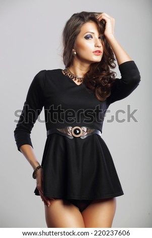 Portrait of fashionable sexy woman in black dress studio light background