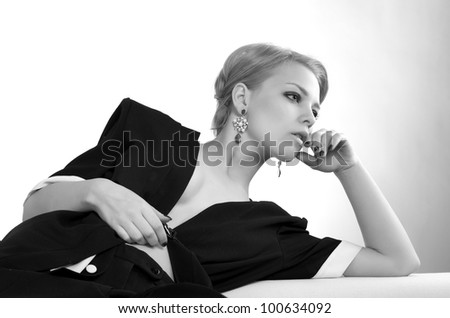 Portrait of fashionable sexy woman lying on the top of sofa - stock photo