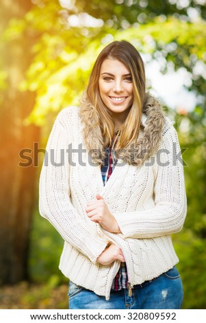 Portrait of fashionable teenage blonde girl in beige sweater in autumn posing and smiling. Cute young woman in trendy fall outfit outdoors in park. Vertical, vibrant colors, retouched. - stock photo