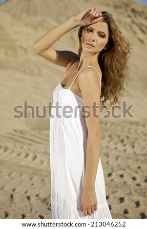 Portrait of fashionable young adult attractive and sensuality brunette woman in white dress dancing on the desert - stock photo