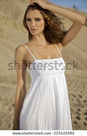 Portrait of fashionable young adult attractive and sensuality sexy beauty brunette woman in white elegance dress on the desert - stock photo