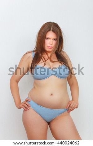 Portrait of fat woman in underwear or lingerie posing with her hands on hips in studio. Red haired lady looking disappointed or sad. - stock photo