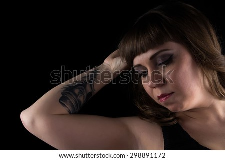 Portrait of fat woman with tattoo on hand on black background