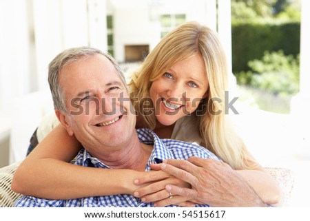 Portrait Of Father And Adult Daughter Relaxing On Sofa - stock photo