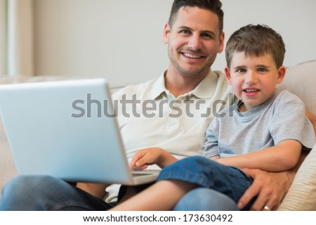 Portrait of father and boy with laptop sitting on sofa at home - stock photo