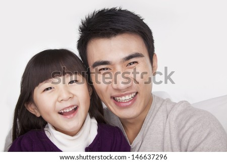 Portrait of father and daughter, studio shot - stock photo