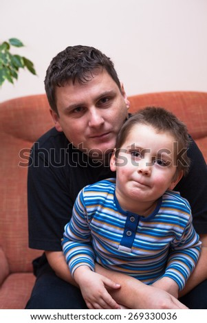 Portrait of father and his child boy, sitting on sofa at home - stock photo