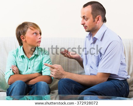 Portrait of father and his teenager son having serious conversation indoors - stock photo