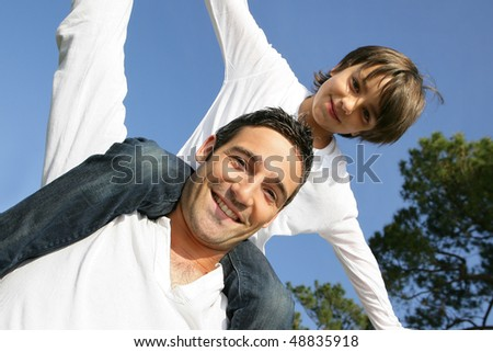 Portrait of father and son doing piggyback - stock photo