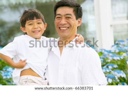 Portrait of father and son laughing - stock photo