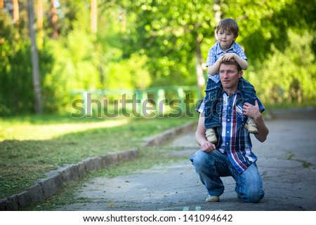 Portrait of father and son play outdoors - stock photo
