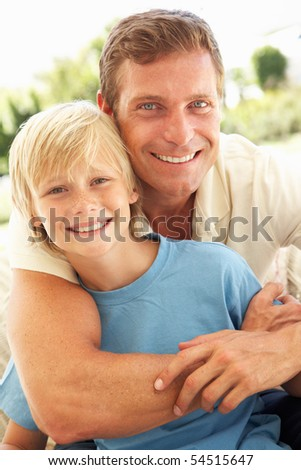 Portrait Of Father And Son Relaxing On Sofa