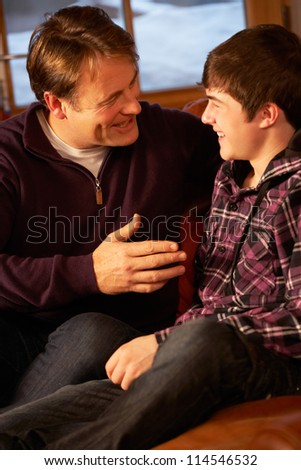 Portrait Of Father And Son Relaxing On Sofa Together - stock photo
