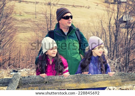 Portrait of Father and two daughters  in the mountains.Cross processed. - stock photo