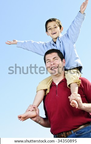 Portrait of father giving shoulder ride to son - stock photo