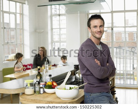 Portrait of father standing arms crossed at kitchen counter while family sitting in background - stock photo