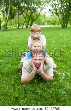 Portrait of father with two sons outdoor in summer park - stock photo