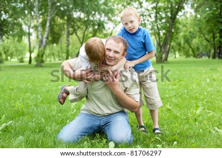 Portrait of father with two sons outdoor in summer park