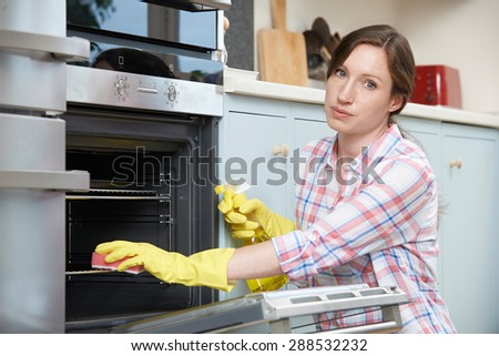 Portrait Of Fed Up Woman Cleaning Oven - stock photo