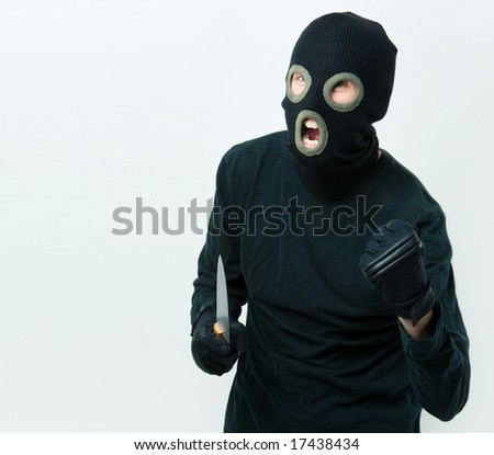Portrait of felon in balaclava with knife in gloved hand