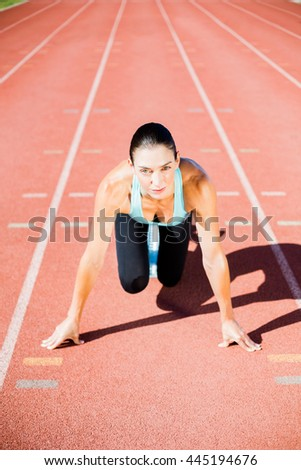 Portrait of female athlete ready to run on running tracks - stock photo