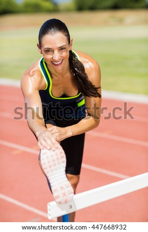 Portrait of female athlete warming up above hurdle on running track - stock photo
