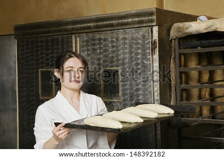 Portrait of female baker carrying loaves of bread bough to bake - stock photo