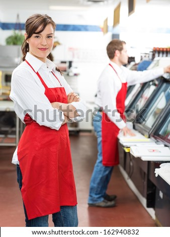 Portrait of female butcher standing arms crossed with colleague working in background at store