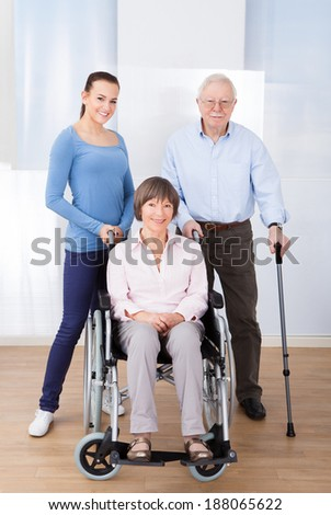 Portrait of female caregiver with disabled senior couple at nursing home