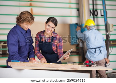 Portrait of female carpenter holding digital tablet while standing by colleague in workshop - stock photo