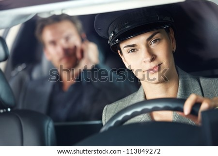 Portrait of female chauffeur in luxury car. - stock photo