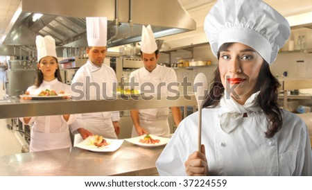 portrait of female chef and her assistants in the kitchen - stock photo