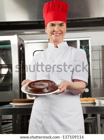 Portrait of female chef presenting chocolate cake in industrial kitchen