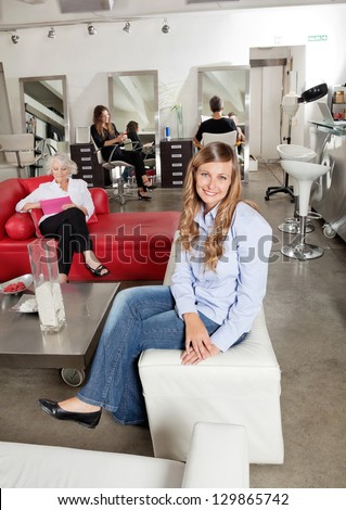 Portrait of female client smiling with customers in background at salon - stock photo