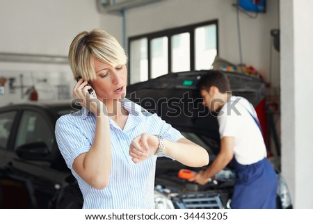 portrait of female client talking on mobile phone in auto repair shop. - stock photo