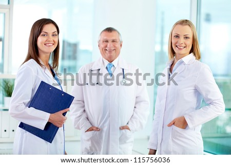 Portrait of female clinicians looking at camera with senior doctor on background - stock photo