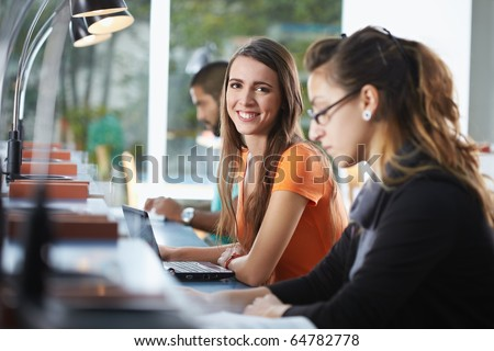 portrait of female college student sitting in library with laptop computer and looking at camera. Horizontal shape, side view, waist up