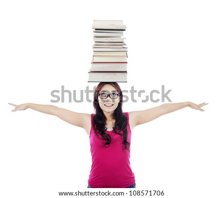 Portrait of female college student stretches her hands with a pile of books on her head - stock photo