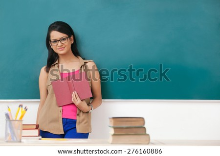 Portrait of female college student with a book - stock photo