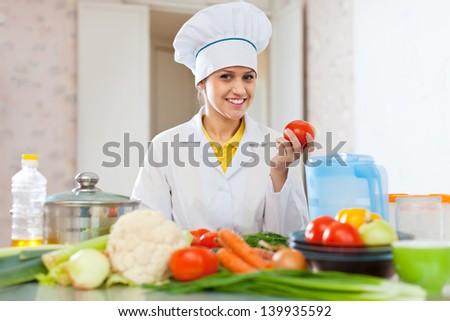 Portrait of female cook  with vegetables in kitchen