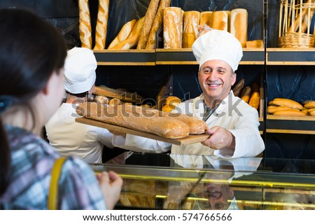Portrait of female customer buying fresh bread from cheerful baker