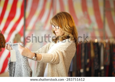 Portrait of female customer standing in clothing store and holding sweatshirt in her hands. Small business. - stock photo