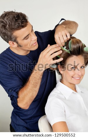Portrait of female customer with hairstylist curling hair at beauty parlor - stock photo