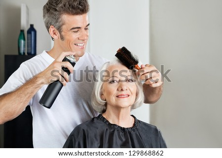 Portrait of female customer with hairstylist setting up hair at beauty parlor - stock photo