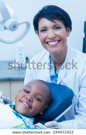 Portrait of female dentist examining a boys teeth in the dentists chair - stock photo