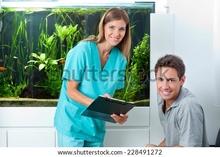 Portrait of female dentist holding clipboard with male patient in clinic - stock photo