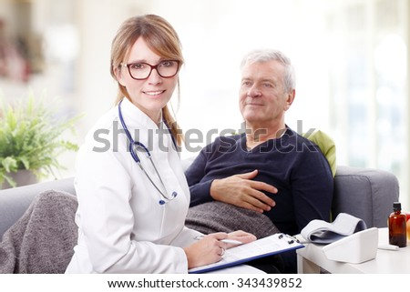 Portrait of female doctor holding in her hand a clipboard and consulting with old patient while sitting at nursing home.