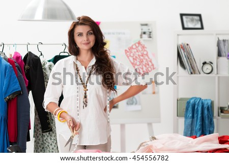 Portrait of female dress maker standing at her atelier and holding pair of tailor scissors. Successful adult business woman employed at her own business.