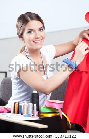 Portrait of female dressmaker adjusting clothes. - stock photo