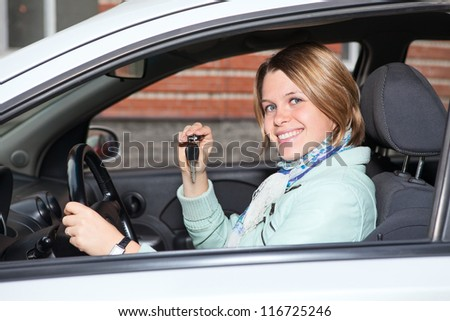 Portrait of female driver with car key in hand - stock photo